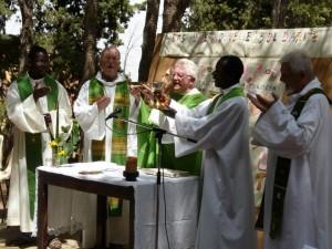 Chrislain avec Mgr Georger et prêtres durant messe